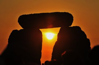 WILTSHIRE, ENGLAND - JUNE 21: Revellers watch sunrise over Stonehenge during celebrations to mark the summer solstice at the prehistoric monument on June 21, 2014 in Wiltshire, England. An estimated 37,000 revellers and modern day druids gathered at Stonehenge, a tradition dating back thousands of years, to celebrate the solstice and watch the sunrise. (Photo by Rufus Cox/Getty Images)